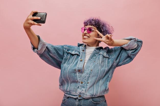 眼鏡の巻き毛の面白い女性が写真を撮り、ピースサインを表示します。特大のジャケットのポーズで明るい女性。