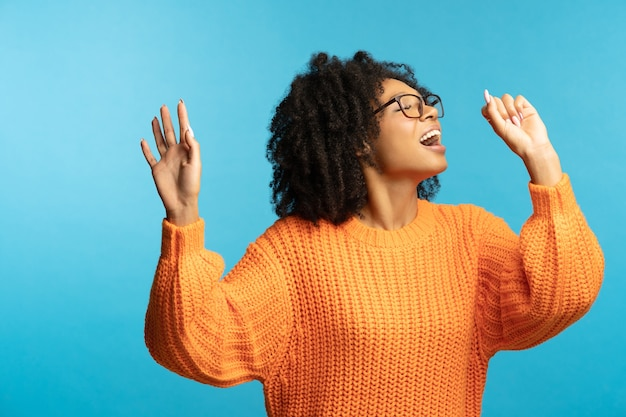 Funny woman with curly hair sings her favorite song, dancing, wear orange sweater, isolated on blue