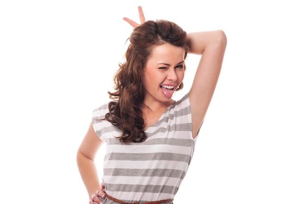 舌を突き出している角を持つ面白い女性