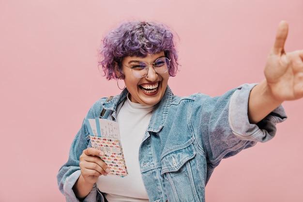 Donna divertente con piercing al naso in occhiali rotondi e grandi orecchini ride e tiene biglietti e passaporto.