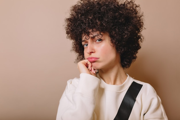 Funny woman with playfully puffed lips poses on beige