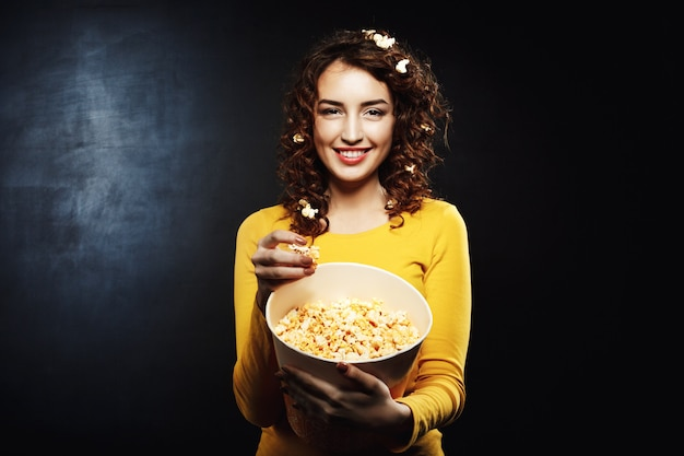 Funny woman with popcorn on hair smiling and looking straight