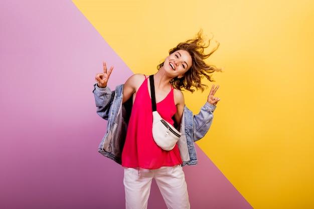 Donna divertente con i capelli corti ondulati ballare e divertirsi sul multicolor.