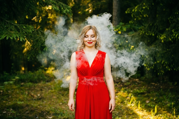 Funny woman with smiling face wearing red dress and standing in clouds of smoke in the forest.
