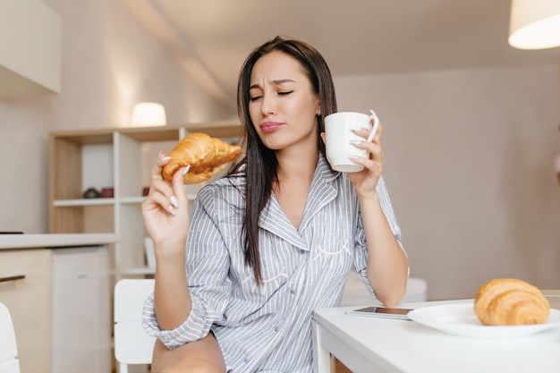 Funny woman with straight black hair eating croissant during breakfast in cozy apartments