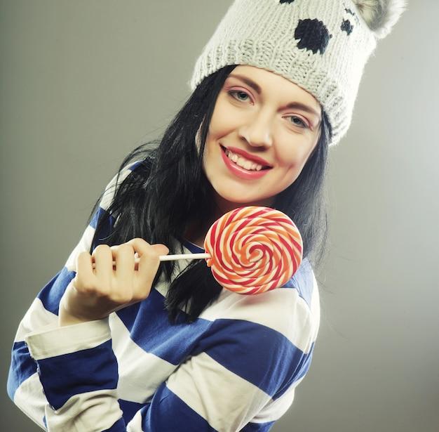 大きなロリポップを保持している冬の帽子を持つ面白い女性