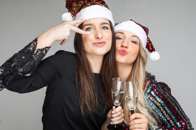Donne divertenti in abiti e cappelli natalizi bevono champagne e posano per la telecamera