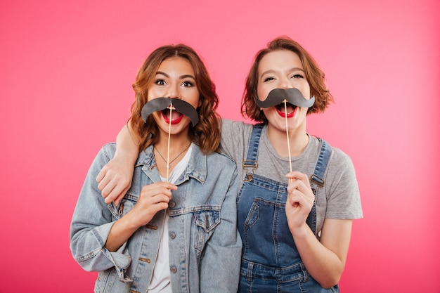 Funny women friends holding fake moustache.