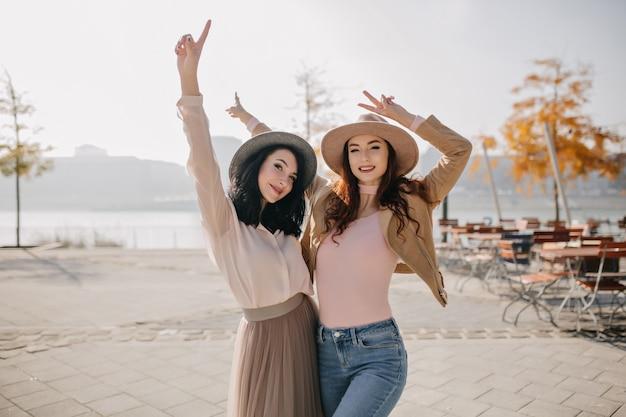 Donne divertenti in cappelli che ballano nella piazza della città con alberi gialli