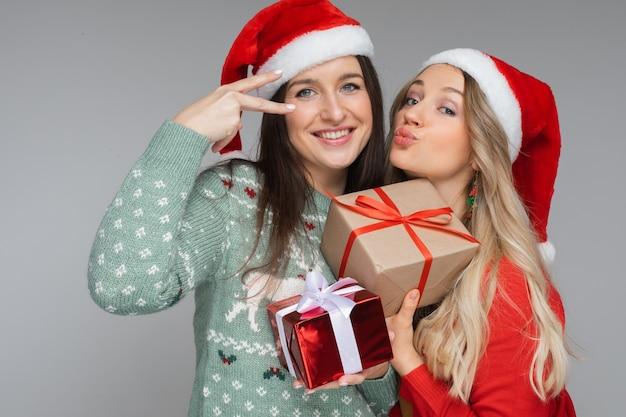 빨간색과 흰색 크리스마스 모자를 쓴 재미있는 여성들은 서로를 위한 선물을 들고 카메라를 위해 포즈를 취합니다.