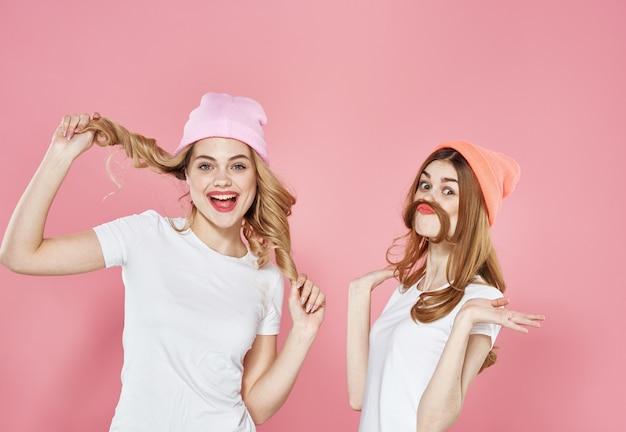 T- 셔츠 매력적인 모자에 재미 있은 여자보기 핑크 벽을 잘립니다.