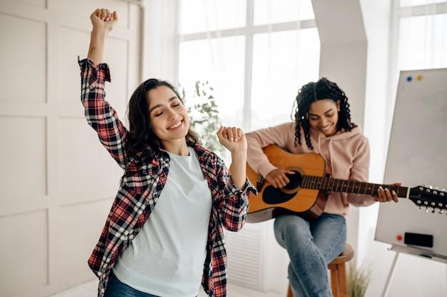 Смешные женщины играют на гитаре и танцуют дома. симпатичные подружки в наушниках отдыхают в комнате, любители звука отдыхают на диване, подруги отдыхают вместе