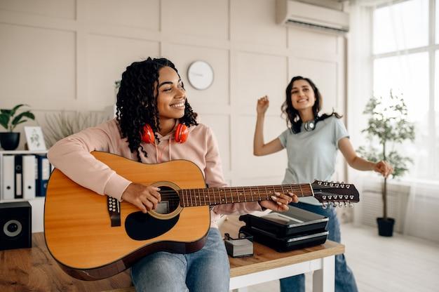 面白い女性がギターを弾き、家で音楽を聴いています。イヤホンをしたかわいいガールフレンドが部屋でくつろぎ、音の愛好家がソファで休んで、女性の友達が一緒にレジャーをする