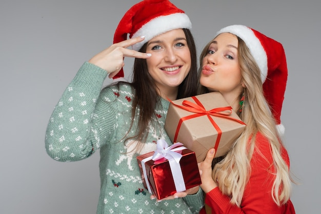 Donne divertenti con cappelli natalizi rossi e bianchi si tengono regali l'una per l'altra e posano per la telecamera
