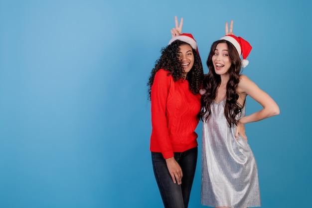 크리스마스 모자와 파란색 위에 절연 축제 옷을 입고 재미있는 여자