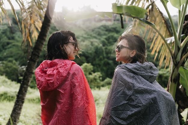 숲 주위를 산책하는 동안 서로보고 젖은 머리를 가진 재미있는 여자. 자연에 서있는 비옷에 여성 관광객의 야외 사진.