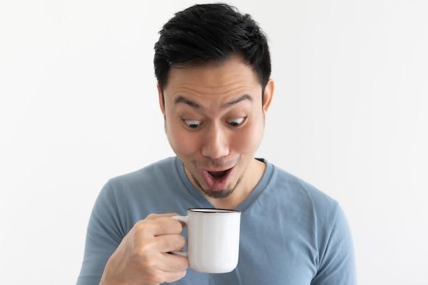 Funny wow face of asian man in blue t-shirt drinks coffee from white mug.