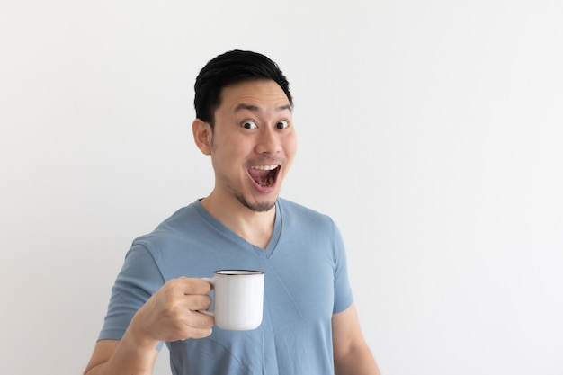 Funny wow face of man in blue tshirt drinks coffee from white mug