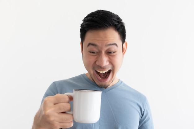 青いtシャツを着た男の面白いすごい顔は白いマグカップからコーヒーを飲みます。