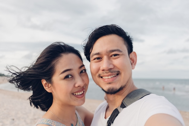 Funny wow face selfie of couple on beach.