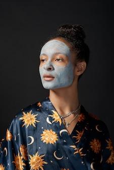 Смешная девушка юн с глиняной маской красоты на коже изолировала модель