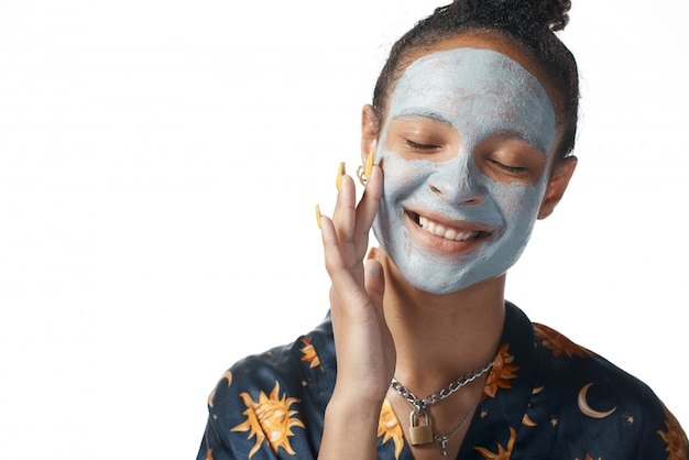 Funny yong girl with clay beauty mask on skin isolated model
