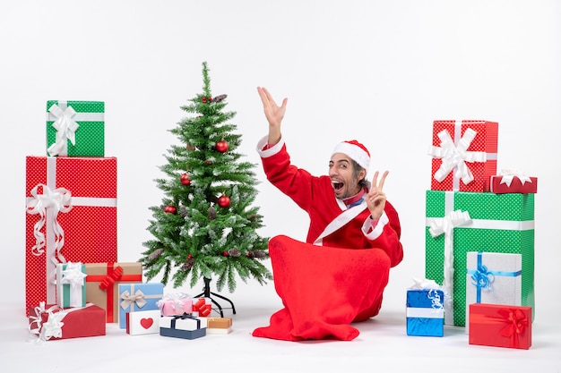 プレゼントとサンタクロースに扮した面白い若い大人と白い背景の上の勝利のジェスチャーを作る上を指している地面に座って飾られたクリスマスツリー