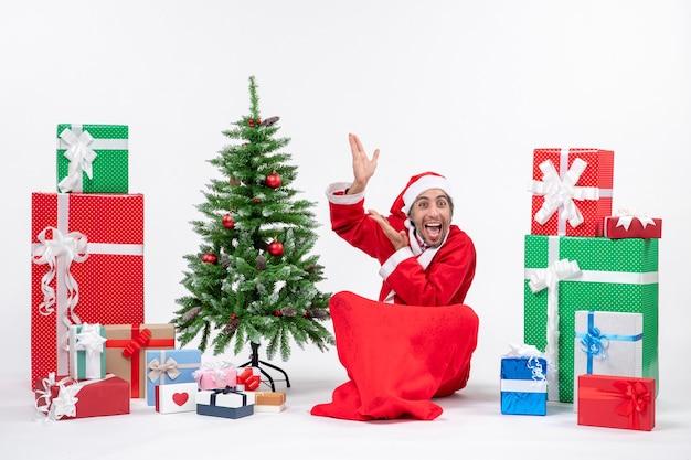 Забавный молодой человек в костюме санта-клауса с подарками и украшенной елкой сидит на земле, указывая вверху на белом фоне