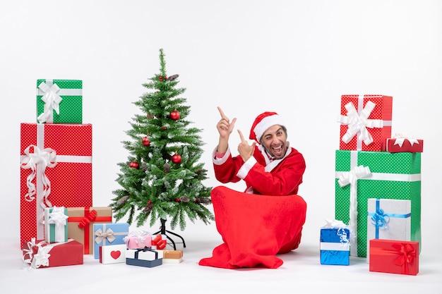白い背景の右側に何かを指している地面に座って贈り物と飾られたクリスマスツリーでサンタクロースに扮した面白い若い大人