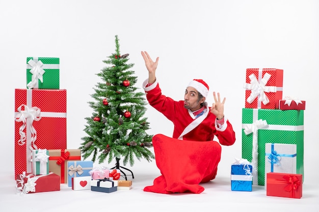 Funny young adult dressed as santa claus with gifts and decorated christmas tree sitting on the ground pointing above making eyeglasses gesture on white background