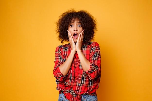 面白い若いアフリカ女性がオレンジ色の背景に分離されたポーズします。驚きの顔。スタジオ撮影。