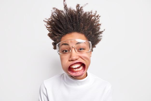 재미있는 젊은 아프리카 계 미국인 여자 입 벌리고 투명 안경을 쓰고 큰 소리로 외친다.