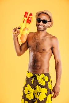 オレンジ色の壁に水鉄砲を保持している水着の面白い若いアフロ男