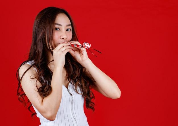 재미 있는 젊고 치료 아시아 여자 재생 및 파티 휘파람을 불고. 스튜디오 빨간색 배경에 쐈 어.