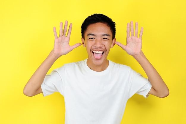 黄色の背景に分離された、ばかげた顔を叫んで面白い若いアジア人