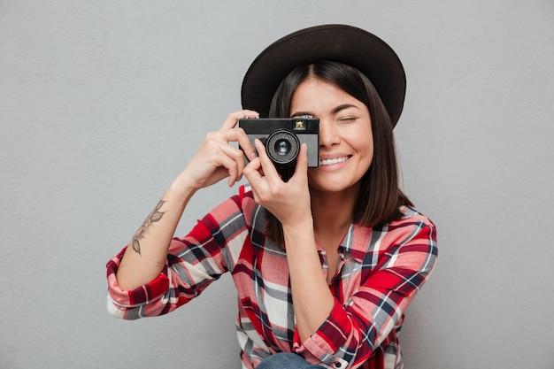 カメラを保持している灰色の壁に分離された面白い若いアジア女性。