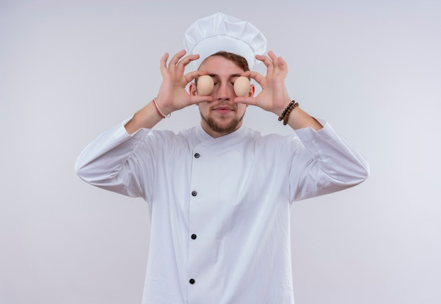 Un divertente giovane chef barbuto uomo che indossa l'uniforme bianca del fornello e il cappello che tiene le uova biologiche davanti ai suoi occhi su una parete bianca