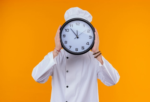 A funny young bearded chef man in white uniform holding wall clock in front of his face on an orange wall