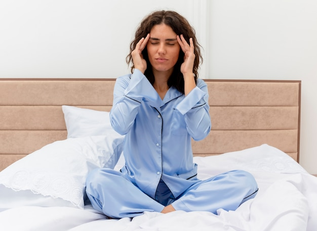 Funny young beautiful woman in blue pajamas sitting on bed touching temples looking unwell having headache in bedroom interior