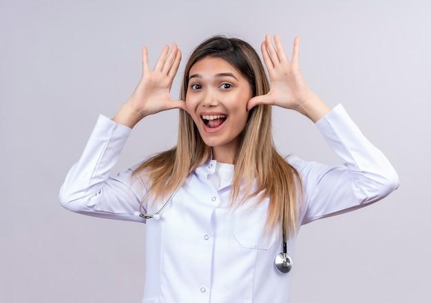 Divertente giovane bella donna medico indossa camice bianco con lo stetoscopio che sorride allegramente con le palme aperte vicino al viso