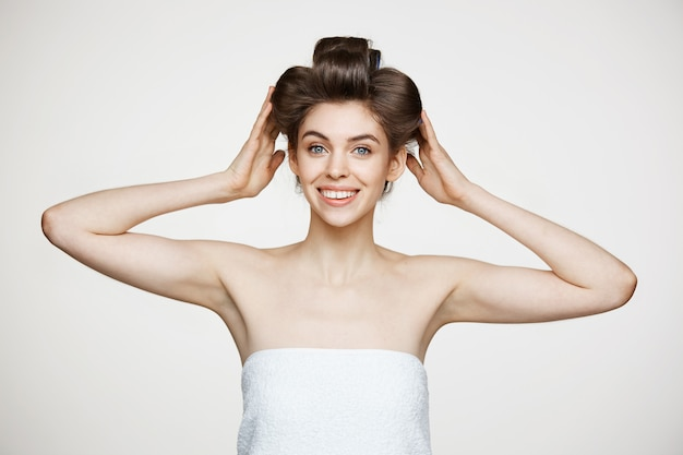 Funny young beautiful woman in hair curlers and towel posing. beauty cosmetology and spa.