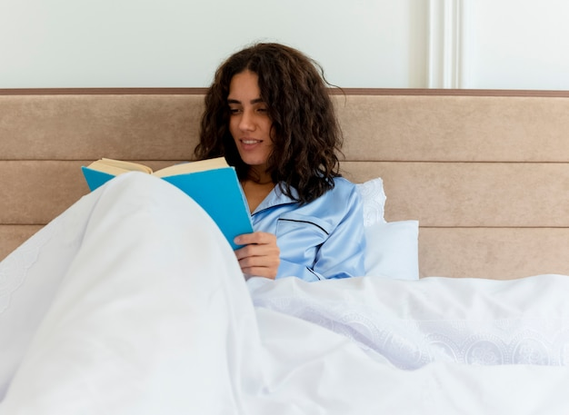 밝은 배경에 침실 인테리어에서 주말을 즐기는 침대 독서 책에 앉아 파란색 잠옷에 재미 젊은 아름 다운 여자