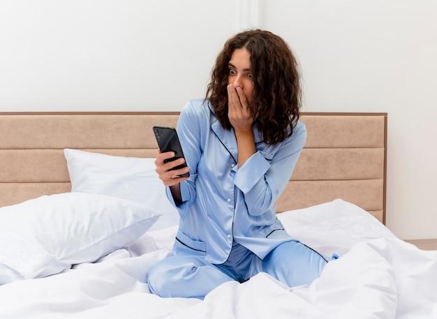 スマートフォンを使用してベッドに座っている青いパジャマを着た面白い若い美しい女性が寝室のインテリアで驚いて驚いているように見える