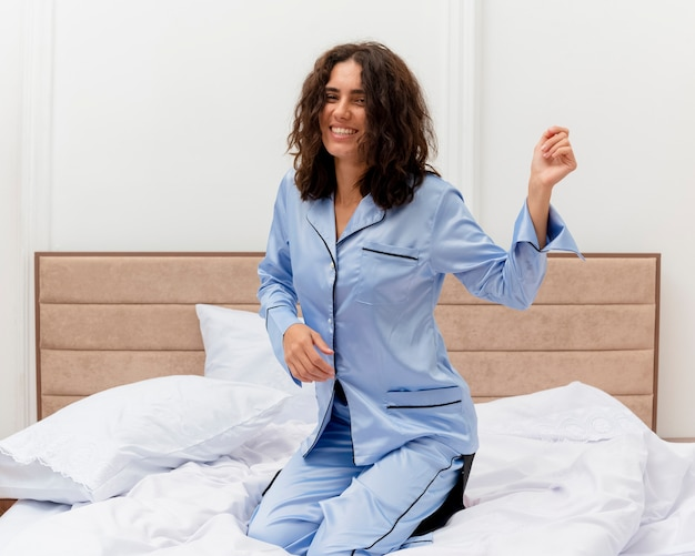 明るい背景の寝室のインテリアで元気に幸せで前向きな笑顔とコーヒーのカップとベッドに座っている青いパジャマの面白い若い美しい女性