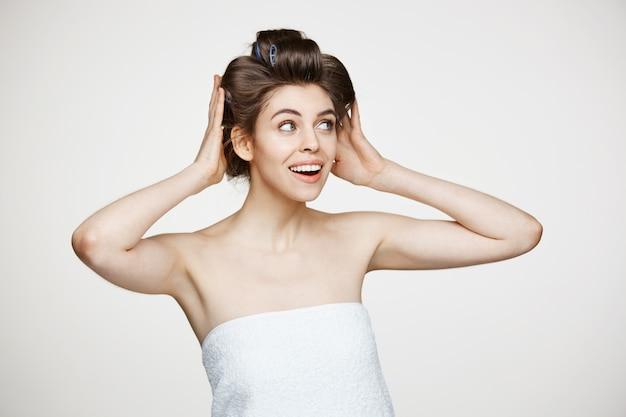 ヘアカーラーとタオルのポーズで面白いの若い美しい女性。美容美容とスパ。