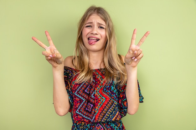 Funny young blonde slavic girl stucking out her tongue and gesturing victory sign