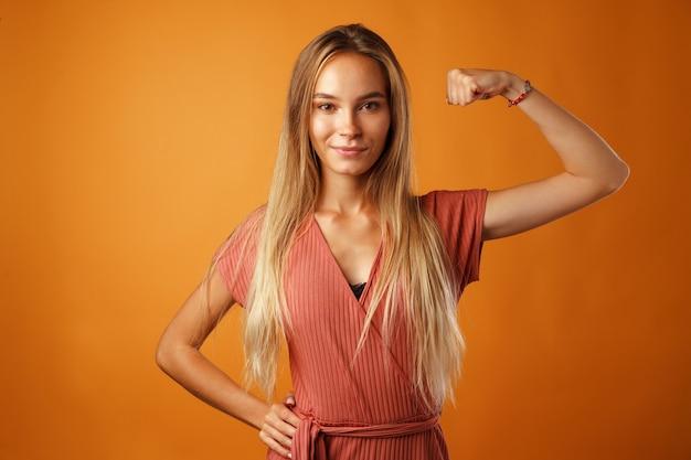 Смешная молодая блондинка показывает, насколько сильны ее руки против апельсина