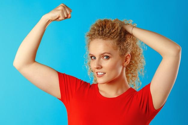 Смешная молодая блондинка показывает, насколько сильны ее руки