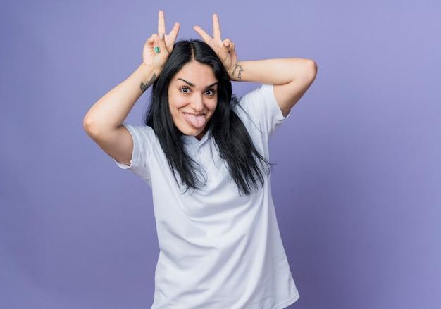 재미있는 젊은 갈색 머리 백인 여자 머리 몸짓 뿔에 손을 보유 하 고 보라색 벽에 고립 된 혀를 튀어 나와