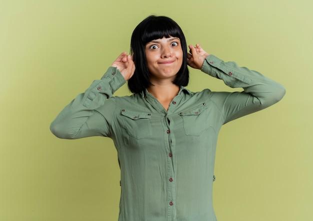 재미있는 젊은 갈색 머리 백인 여자 복사 공간 올리브 녹색 배경에 고립 된 사원에 손가락을 넣습니다.